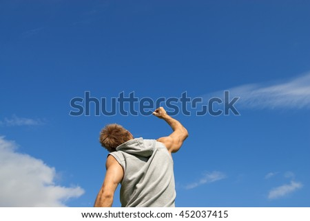 Sporty young man with his arm raised in joy, on blue sky background.