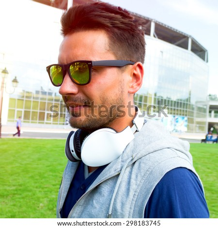 Sporty young man working out at early morning while crossfit training on green grass background, male jogger exercising while listening to music with wireless headphones, runner working out outdoors - stock photo