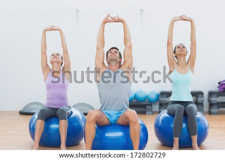 Sporty young people sitting on exercise balls and stretching up hands in the gym - stock photo