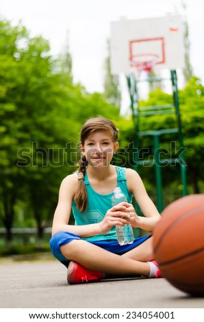 Sporty young teenage girl on a basketball court sitting cross legged under the goal drinking a bottle of water with the ball in the foreground - stock photo