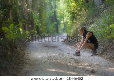 Sporty young woman binds the shoe among a woods trail - stock photo