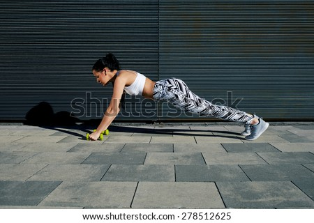 Sporty young woman doing press ups with dumbbells while standing on black background outdoors,female in workout gear doing push-ups with some weights against wall with copy space for your text message - stock photo