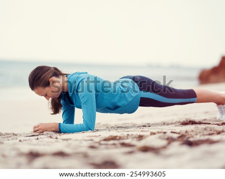 Sporty young woman exercising  on the sea coast - stock photo