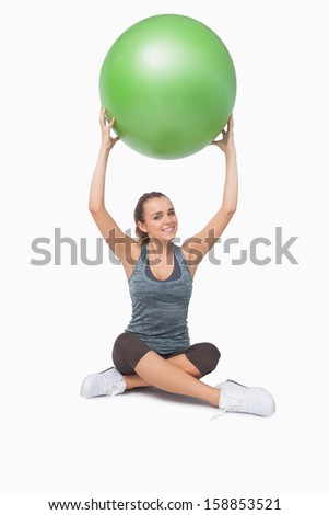 Sporty young woman lifting a green fitness ball smiling at camera