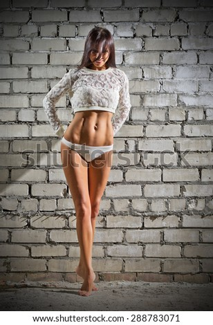 Sporty young woman on grey brick wall background (normal version) - stock photo