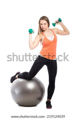 Sporty young woman posing with a fit and dumbbells. Isolated on white