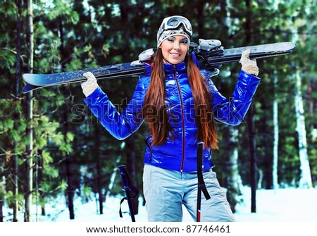 Sporty young woman posing with her skis outdoor. - stock photo