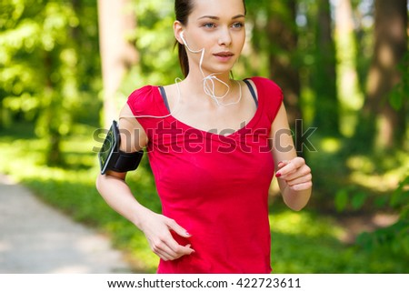 Sporty young woman running in the park and listening to music. Sport lifestyle.