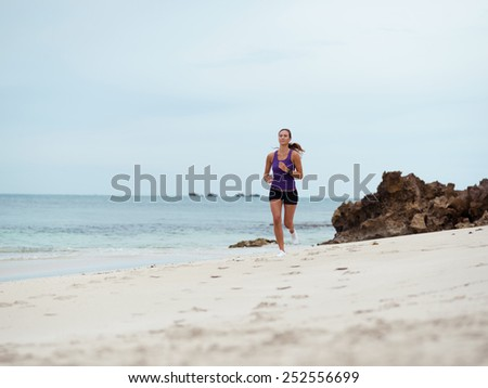 Sporty young woman running on the sea coast