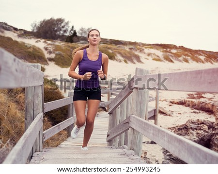 Sporty young woman running up the stairs - stock photo