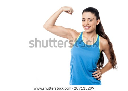 Sporty young woman showing her biceps