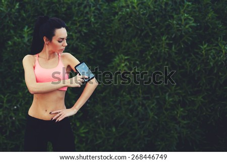 Sporty young woman standing in the park with big copy space for text while getting ready for workout,healthy fit runner setting her personal trainer application or stopwatch on cell phone before a run - stock photo