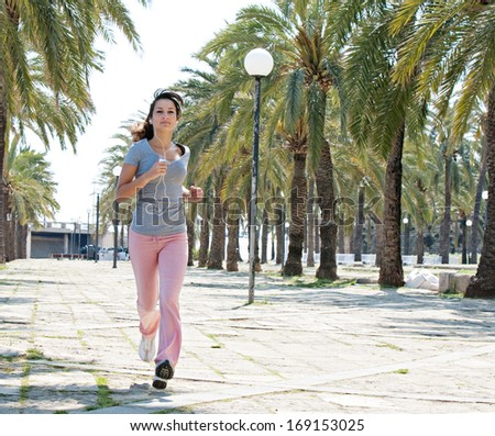 Sporty young woman training and running on a stone pavement avenue with aligned palm trees during a sunny summer day while listening to music on her smartphone and headphones, outdoors. - stock photo