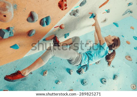 Sporty young woman training in a colorful climbing gym. Free climber girl climbing up indoor - stock photo