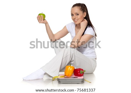 Sporty young woman with scales, fresh peppers and apple on a white background.  Concept of healthy lifestyle. - stock photo