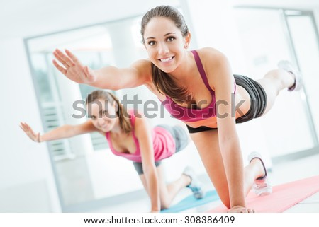 Sporty young women at the gym doing pilates workout on a mat, fitness and healthy lifestyle concept - stock photo
