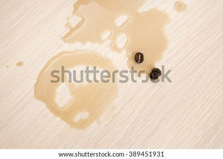 Spot from spilled coffee on the table and coffee beans - stock photo