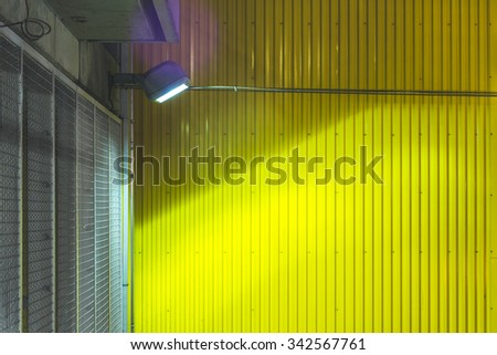 spot light  facing colorful yellow metal texture surface in the parking lot. - stock photo