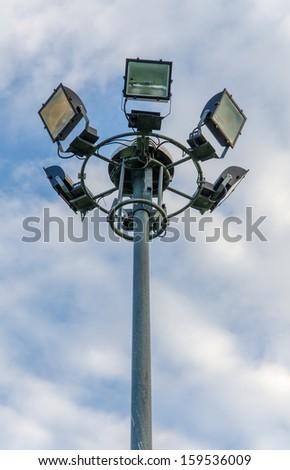 Spot light tower in blue sky. - stock photo