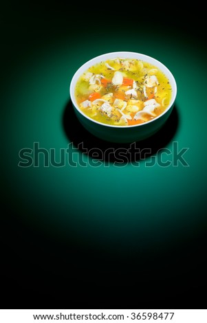 Spot of bright light on bowl of nice chicken soup - stock photo