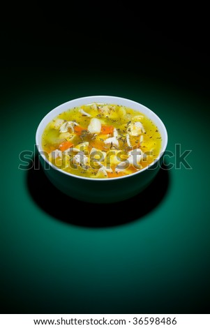 Spot of light on bowl of hot soup on green table - stock photo