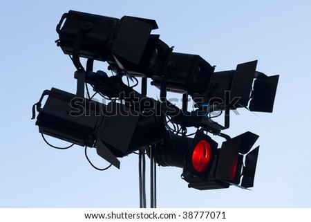 spot stage lights silhouette on blue sky background - stock photo