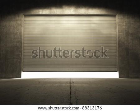Spotlight illuminate building of grungy concrete with roller shutter door - stock photo
