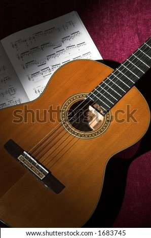 Spotlight on classical guitar with sheet music - stock photo