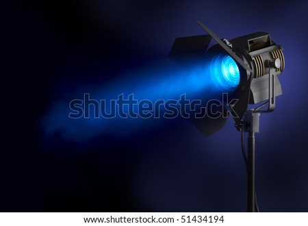 Spotlight shines blue beam of light through smoke, with space for copy