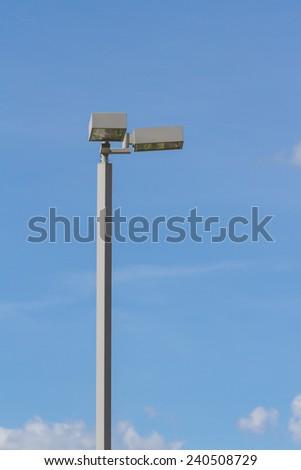 Spotlight tower against blue sky - stock photo