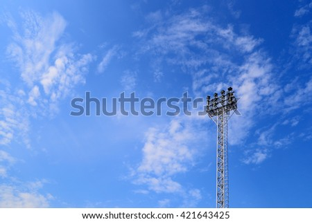 Spotlights lighting tower at an sport arena stadium on blue sky background - stock photo