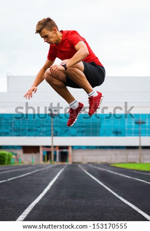 spotrsmen warmingand jamping up before a run. high jump - stock photo