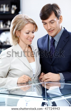 Spouses at a shop show-window consider jeweller ornaments