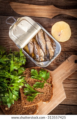 Sprats in oil in a can on a wooden table.