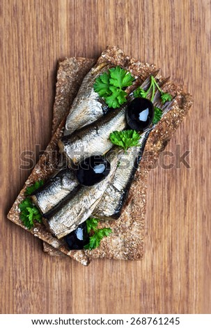 Sprats on crispbread over wooden surface, top view - stock photo