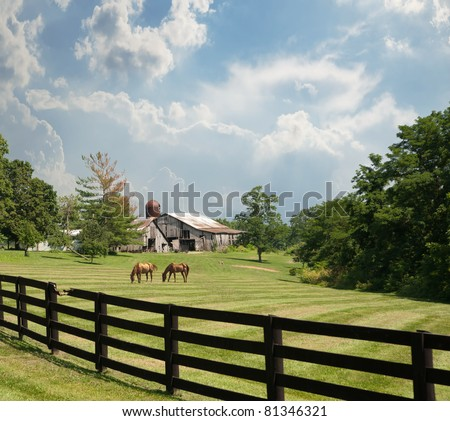 Sprawling acreage of pastures surround a horse farm in Kentucky, USA.  Two horses graze in the pasture with an old rustic barn and silo in the background. - stock photo