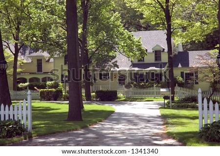 Sprawling Colonial style home. Mature trees and a white picket fence makes this an inviting entrance. Just one of many new house photos in my gallery. - stock photo