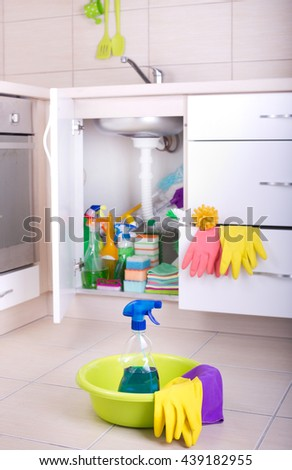 Spray bottle and cleaning tools in washbasin on the floor with supplies stored in kitchen cabinet in background - stock photo