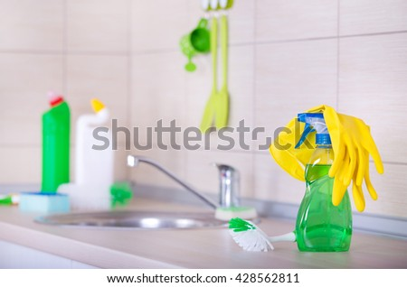 Spray bottle and cleaning tools on the kitchen countertop