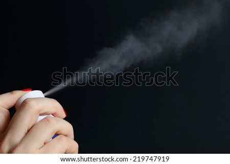 Spray can with fume coming out on black background - stock photo