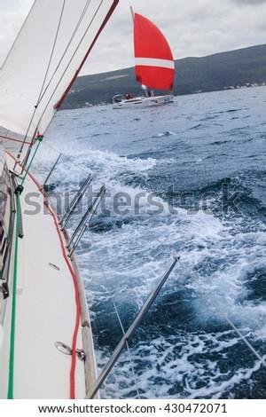 "Spray from the yacht. Tivat, Montenegro - 26 April, 2016. Regatta ""Russian stream"" in God-Katorskaya bay of the Adriatic Sea off the coast of Montenegro. - stock photo"