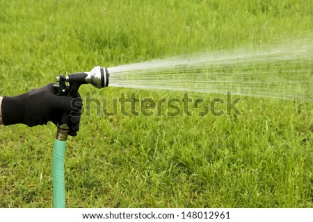 spray of water coming from a garden hose while watering a green grass lawn - stock photo