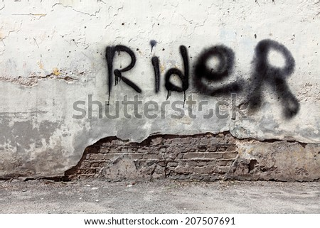 "Spray paint of the word ""Rider"" on a grungy dilapidated concrete wall.  - stock photo"