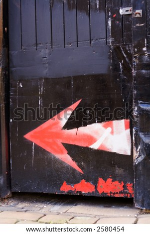 Spray painted arrows on a black gate, fuzzy stenciled signs. - stock photo