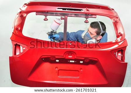 Spraying rear door in red base coat. - stock photo
