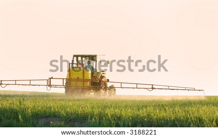 Spraying the Crop. Focus on tractor - stock photo