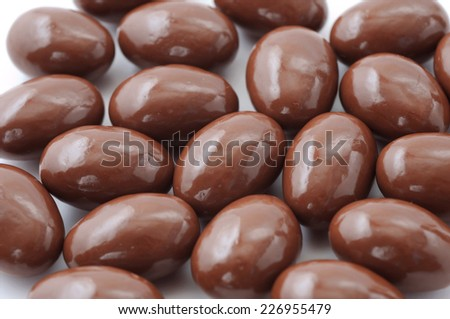 spread of chocolate covered almonds on white background - stock photo