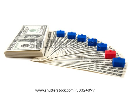 Spread of hundred dollar bills on a white background, with blue houses lined up, one red house indicating odd one out, could be in danger (conceptual) - stock photo