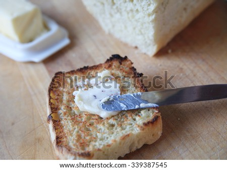Spreading butter on a slice of toast with a butter dish and homemade loaf of bread behind - stock photo