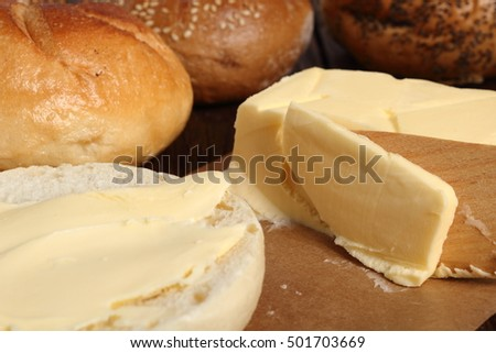 Spreading butter on bread roll